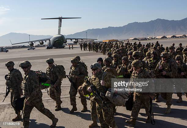 Army soldiers from the 101st Airborne Division march from the back of a C-17 cargo plane May 11, 2013 at Bagram Air Base, Afghanistan. After flying...