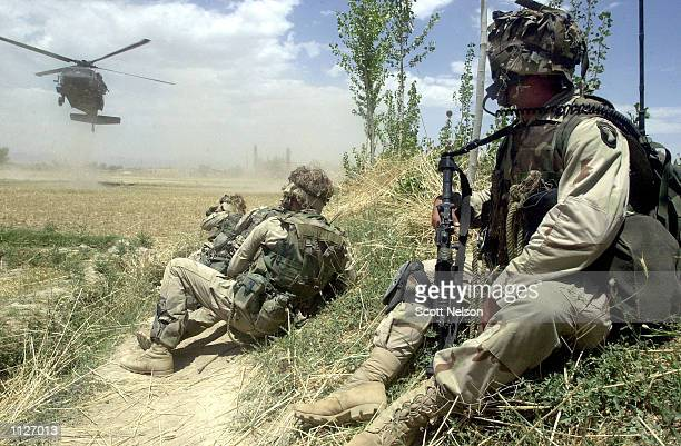 S Army soldiers from the 101st Airborne watch from defensive positions as an inbound Blackhawk helecopter lands July 16 2002 in village of Hesarak...