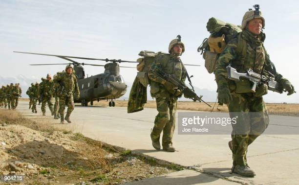 S Army soldiers from the 10th Mountain and the 101st Airborne units disembark from a Chinook helicopter March 11 2002 as they return to Bagram...