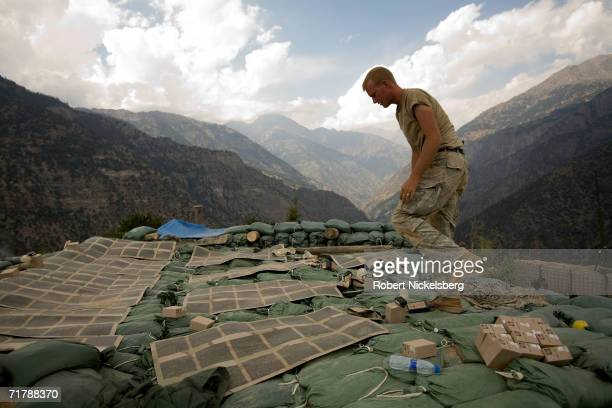 A US Army soldiers from the 10th Mountain Division checks solar powered recharging panels and batteries at a 7000 foot observation post in Kamdesh...