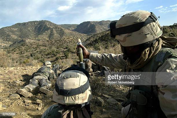 Army soldiers from the 10th Mountain Division fire a 60mm mortar toward the Pakistan border October 19, 2003 where al Qaeda and Taliban forces had...