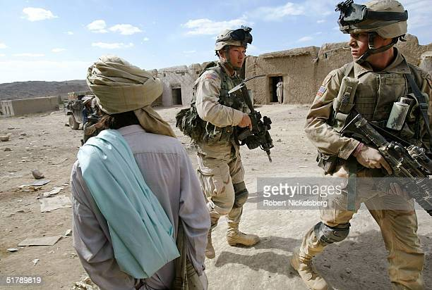 Army soldiers from the 10th Mountain Division , October 19 patrol through Shkin Bazaar in Paktika Province, Afghanistan, as a Pashtun man watches the...