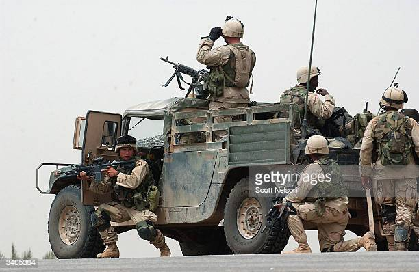 S Army soldiers from the 1st Battalion 14th regiment of the 25th Infantry Division take cover behind their Humvee after coming under fire from...