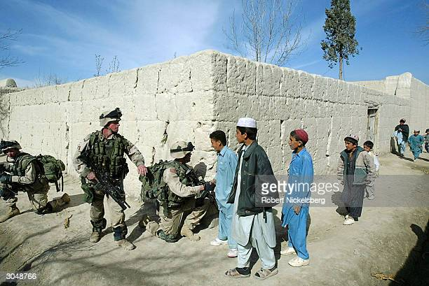 US Army soldiers from the 1st Battalion 501 Parachute Infantry Regiment walk through a village February 14 2004 near the rural outskirts of Khost...