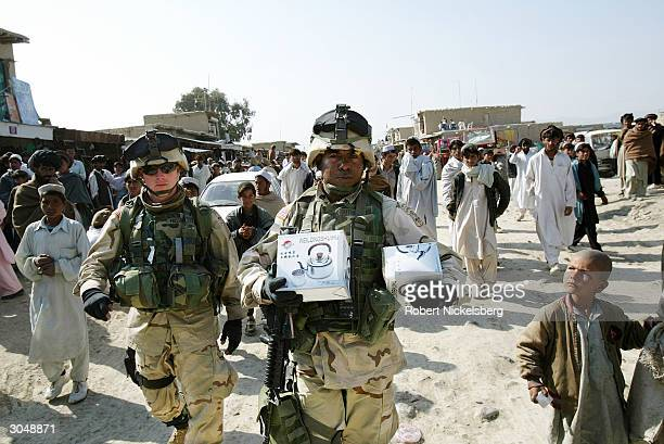 US Army soldiers from the 1st Battalion 501 Parachute Infantry Regiment walk through the Friday market area of Yaqubi Afghanistan February 20 2004...