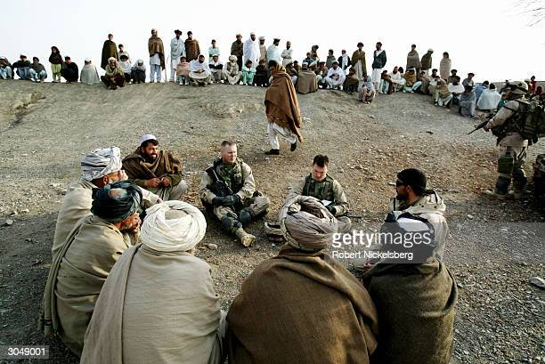 US Army soldiers from the 1st Battalion 501 Parachute Infantry Regiment speak with village elders about former Taliban suspects in the area and for...