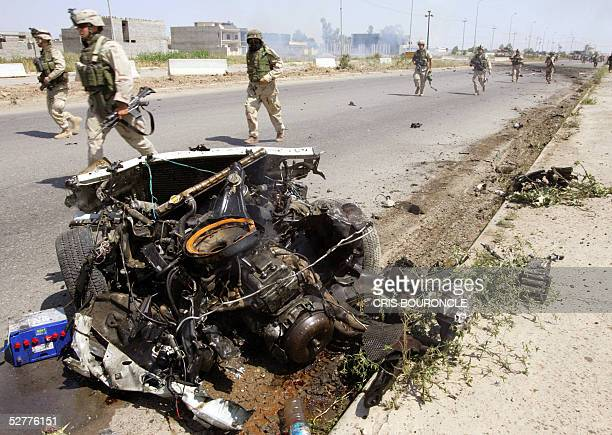 Army soldiers from the 1st Battalion 5th Infantry rush by the charred remains of a suicide car bomb after it detonated between the vehicles of an...