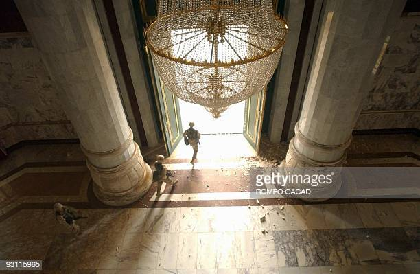 US Army soldiers from the 1st Brigade Combat Team of the 3rd Infantry Division walk out the main entrance of a presidential palace near Baghdad's...