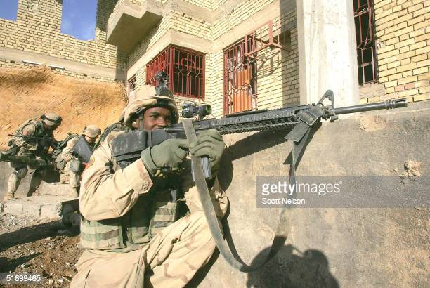 S Army soldiers from the 1st Infantry Division's 2nd Battalion2nd Regiment prepare to seize a building under enemy fire during heavy fighting...