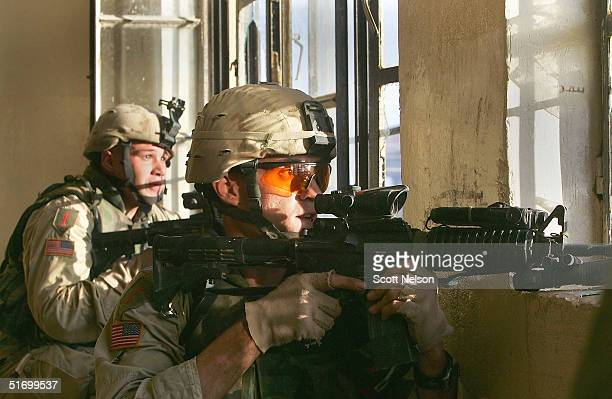 S Army soldiers from the 1st Infantry Division's 2nd Battalion2nd Regiment try to locate an enemy sniper while engaging enemy forces in heavy...
