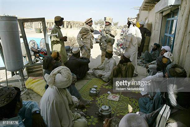 US Army soldiers from the 227th Infantry part of the 25th Infantry Division based in Hawaii speak to locals at a tea shop after an Afghan police...