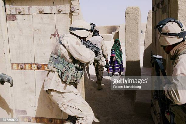 US Army soldiers from the 227th Infantry part of the 25th Infantry Division based in Hawaii approach a private house with an Afghan interpreter...