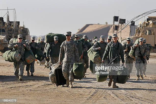Army soldiers from the 2-82 Field Artillery, 3rd Brigade, 1st Cavalry Division, carry their bags to shipping containers as they prepare to leave Camp...