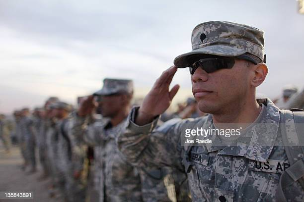 S Army soldiers from the 282 Field Artillery 3rd Brigade 1st Cavalry Division salute during the playing of retreat during the daily flag lowering...