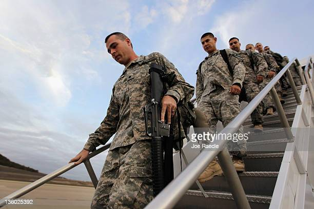 Army soldiers from the 2-82 Field Artillery, 3rd Brigade, 1st Cavalry Division, walk off the plane as they arrive at their home base of Fort Hood,...