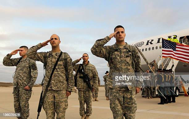 Army soldiers from the 2-82 Field Artillery, 3rd Brigade, 1st Cavalry Division, salute after walking off the plane as they arrive at their home base...