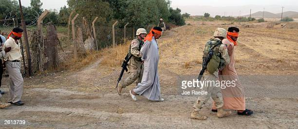 Army soldiers from the 299th Engineering Battalion, 4th Infantry Division walk with blindfolded Iraqi men after capturing them on suspicion they...
