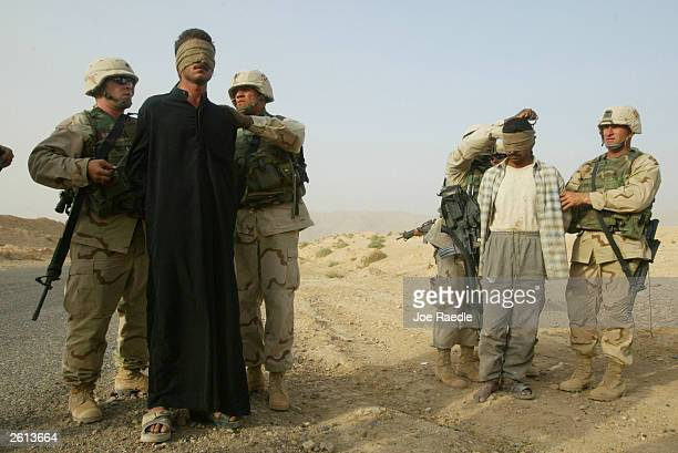 Army soldiers from the 299th Engineering Battalion, Fourth Infantry Division blindfold Iraqi men after capturing them on suspicion they helped attack...