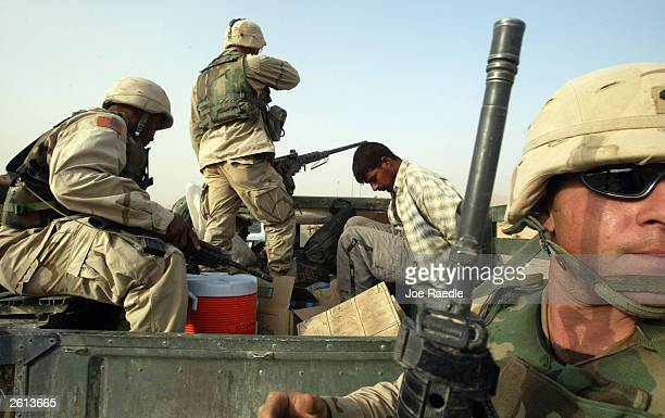 Army soldiers from the 299th Engineering Battalion, Fourth Infantry Division load detained Iraqi men into a truck after suspecting they helped attack...