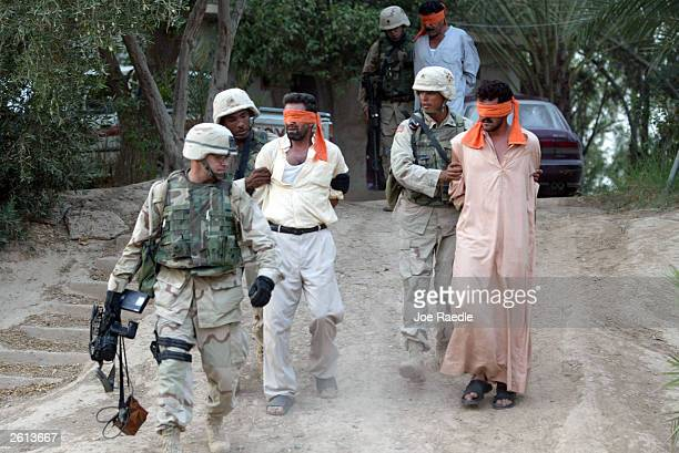 Army soldier's from the 299th Engineering Battalion, Fourth Infantry Division detain Iraqi men suspected of helping attack a convoy today with small...