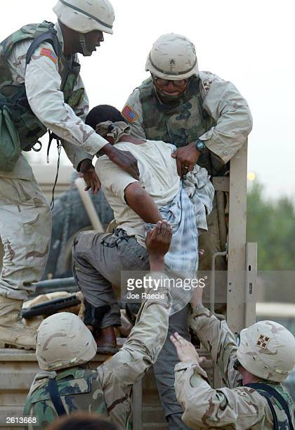 Army soldiers from the 299th Engineering Battalion, Fourth Infantry Division load a detained Iraqi man into a truck after suspecting he helped attack...
