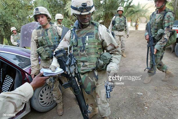 Army soldiers from the 299th Engineering Battalion, Fourth Infantry Division confiscate money and a weapon from a home after being attacked today...