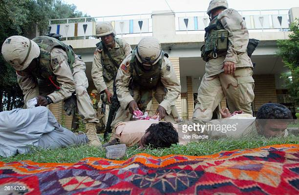 Army soldiers from the 299th Engineering Battalion, Fourth Infantry Division tie the hands of Iraqi men suspected of helping attack a convoy today...
