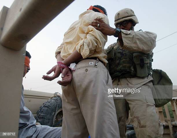 Army soldiers from the 299th Engineering Battalion,4th Infantry Division load a detained Iraqi man into a truck after suspecting he helped attack a...