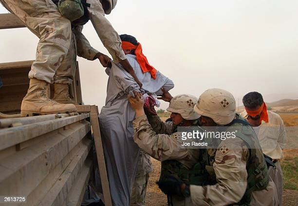 Army soldiers from the 299th Engineering Battalion,4th Infantry Division load detained Iraqi man into a truck after suspecting they helped attack a...