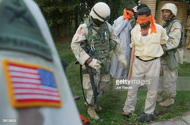 Army soldiers from the 299th Engineering Battalion,4th Infantry Division blindfold Iraqi men after capturing them on suspicion they helped attack a...