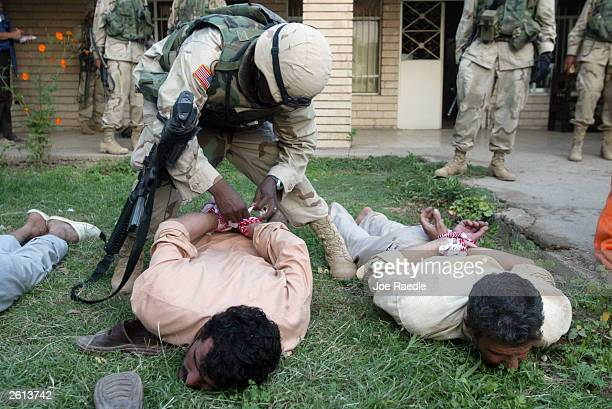Army soldiers from the 299th Engineering Battalion,4th Infantry Division tie the hands of Iraqi men suspected of helping attack a convoy today with...