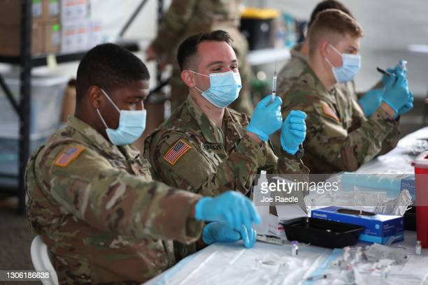 Army soldiers from the 2nd Armored Brigade Combat Team, 1st Infantry Division, prepare Pfizer COVID-19 vaccines to inoculate people at the Miami Dade...