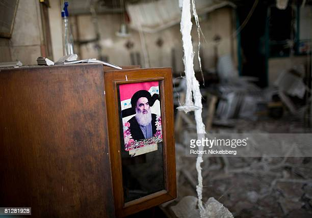 Army soldiers from the 3rd Brigade Combat Team 4th ID move past a destroyed restaurant with a poster of a renowned Shiite cleric to an area where...
