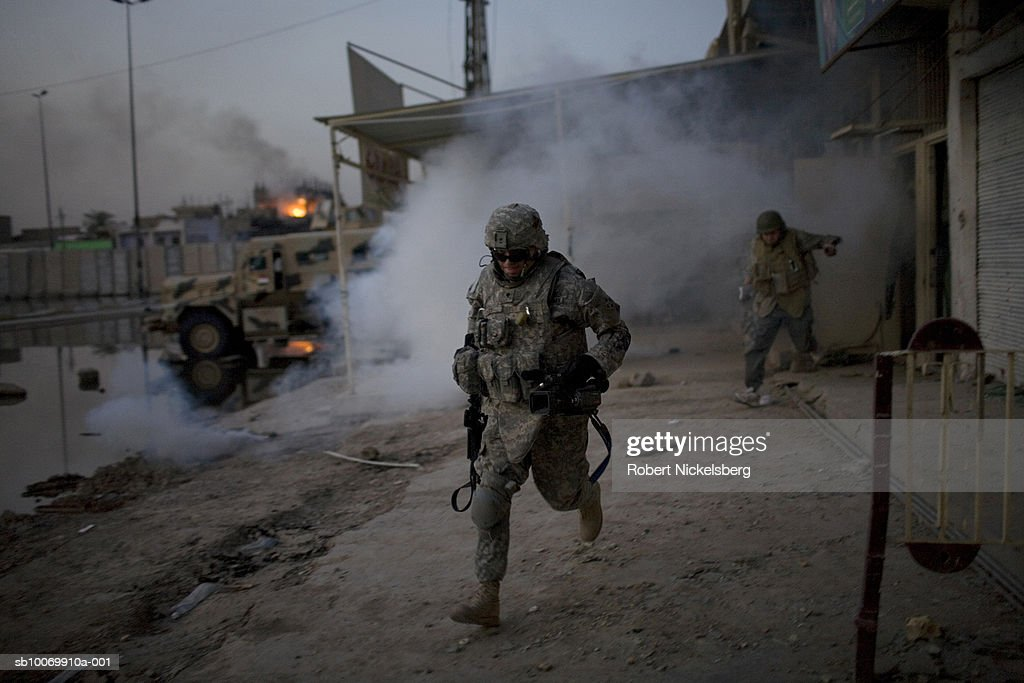 US Army soldiers from the 3rd Brigade Combat Team, 4th ID, run back to their vehicles through smoke from an Iraqi Army position after a US Apache launched Hellfire missile destroyed a floor where a Iraqi militia sniper was firing from north of the wall in Sadr City May 12, 2008 in Baghdad, Iraq. The Iraqi Army position along the contested wall came under sniper fire earlier in the afternoon seriously wounding an Iraqi soldier. Numerous firing incidents occurred on the day a cease fire was declared by Shiite cleric Moktada al-Sadr's militia and Iraqi Army forces inside Sadr City. American forces are in a supporting role for the Iraqi Army operation to disarm the militias north of the frontline.