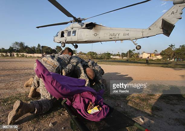 S Army soldiers from the 82nd Airborne cover up an injured women as a Navy helicopter lands to medivac her after she was injured during the...