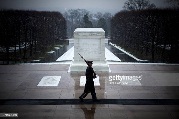 Army soldiers guard the Tomb of the Unknown Soldier at Arlington National Cemetery on December 5 2009 in Arlington Virginia