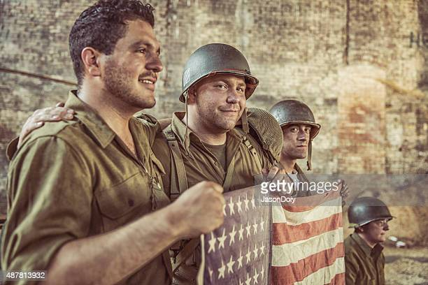 us army soldiers holiding american flag in victory - vj day stock photos and pictures
