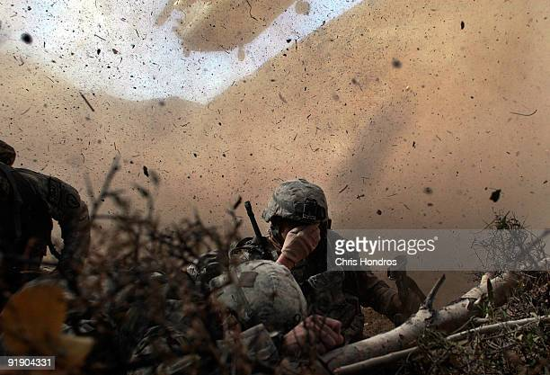 Army soldiers in the 1/501st of the 25th Infantry Division shield their eyes from the powerful rotor wash of a Chinook cargo helicopter as they are...
