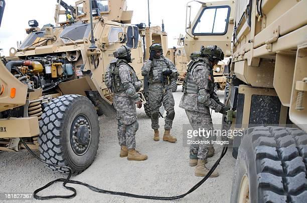 U.S. Army Soldiers jump start a light medium tactical vehicle.