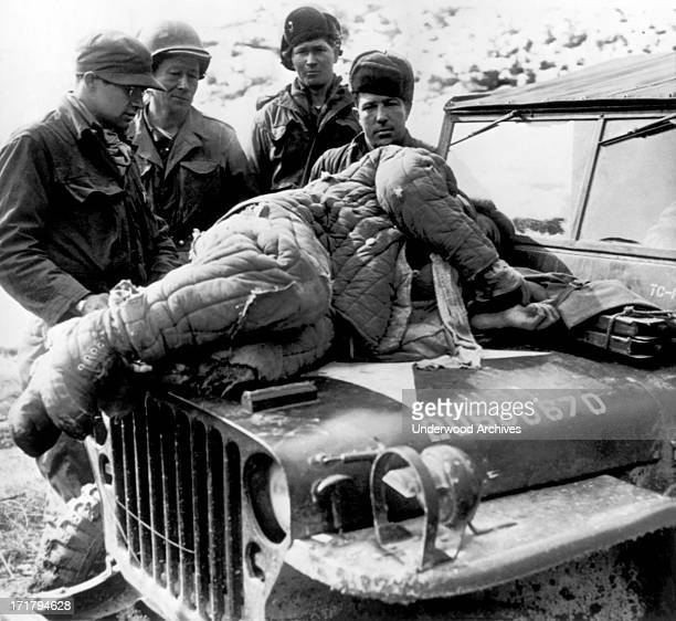US Army soldiers look upon a wounded Chinese Communist soldier that was brought back from the front on the hood of an Army jeep Wonju Korea February...