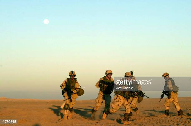 Army soldiers of Task Force 315 of Fort Stewart, Georgia, run towards a trench as they participate in a clearing exercise January 17, 2003 in the...