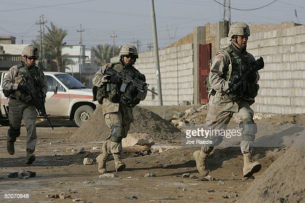 Army soldiers of the 1st Battalion, 503rd Infantry Regiment run after a suspect as they search for the people who mortared the near-by Election Day...