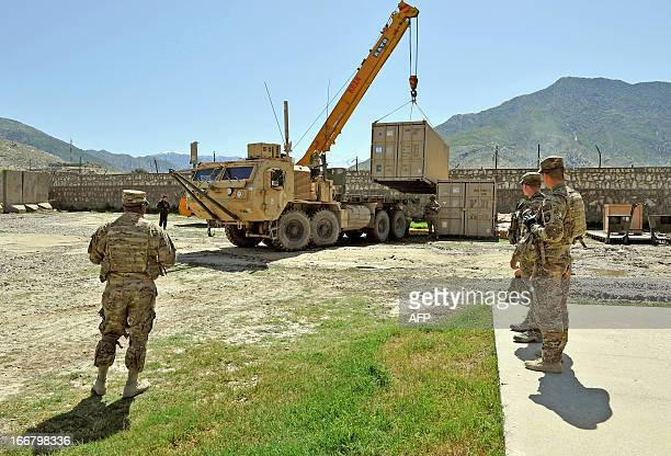 Army soldiers of the 6th Kandak, 1st Brigade Combat Team, 101st Airborne Division watch a crane place a cargo box on a military truck as part of the...