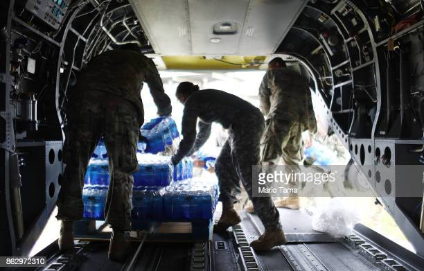 Army soldiers offload bottled water from a helicopter during recovery efforts four weeks after Hurricane Maria struck on October 18, 2017 in Utuado,...