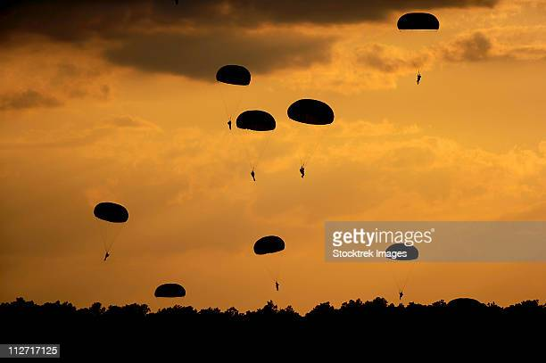 U.S. Army Soldiers parachute through the sky.