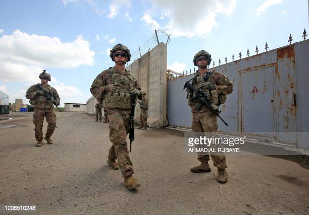 Army soldiers, part of the Combined Joint Task Force Operation Inherent Resolve the US-led coalition against the Islamic State group, walk around at...