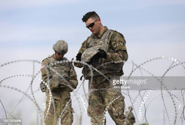 S Army soldiers pause from the heat while stringing razor wire near the port of entry at the USMexico border on November 4 2018 in Donna Texas...