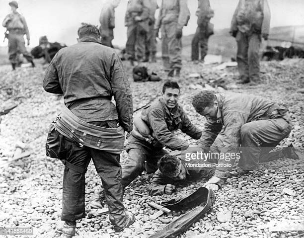 US Army soldiers providing artificial respiration to a fellow soldier who almost drowned on Omaha Beach Normandy June 1944