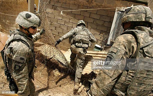 Army soldiers search for a weapons cache in the backyard of a house on June 5 2008 in the alRahmaniya Shiite neighborhood north of Baghdad Iraq US...