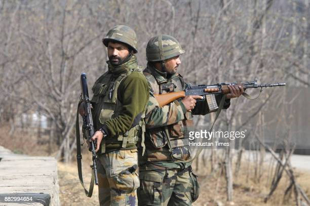 Army soldiers stand guard during a gun battle at Pakherpora village on November 30 2017 south of Srinagar India At least five terrorists were killed...
